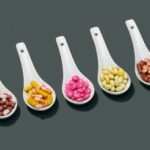 Assorted pills in spoons --- Image by © Paul Linse/Corbis
